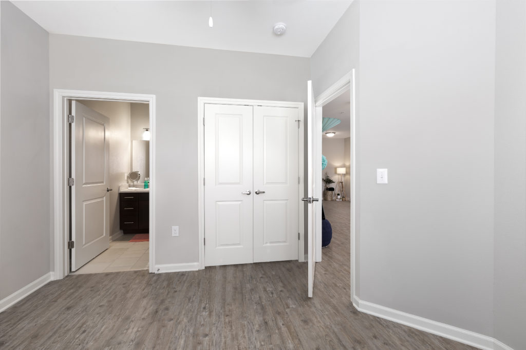 Unfurnished master bedroom with an attached bathroom and hardwood floors